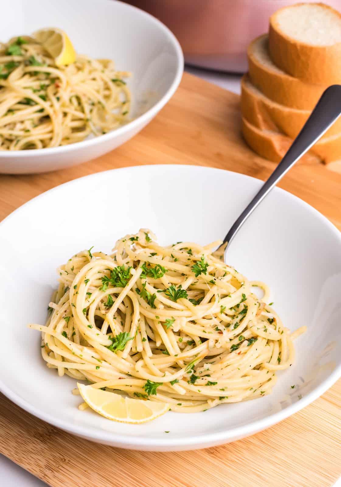 Plated Spaghetti Aglio e Olio in white dish with fork and parsley garnish.