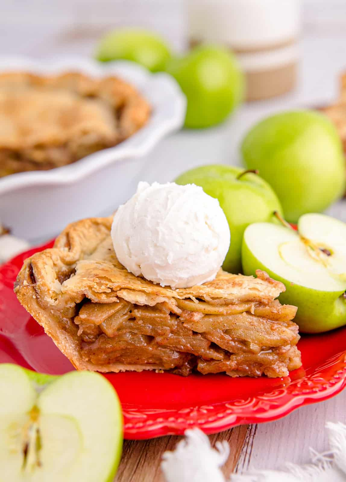 Slice of Apple Pie on red plate with ice cream and apples.