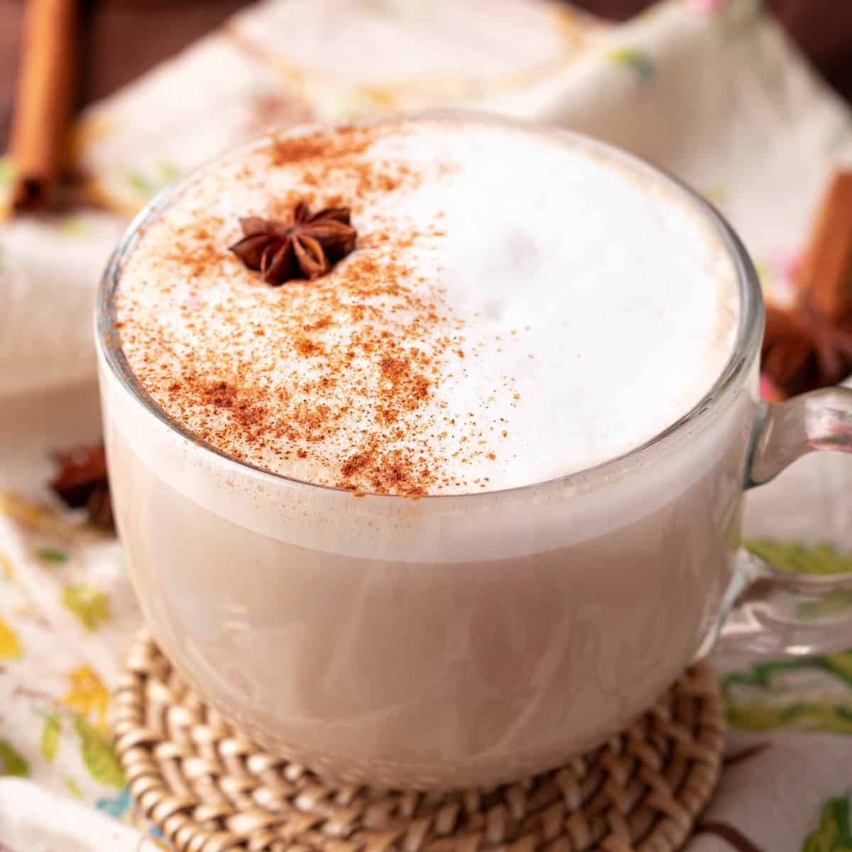 Square image of Chai Latte in mug with cinnamon and a star of anise.