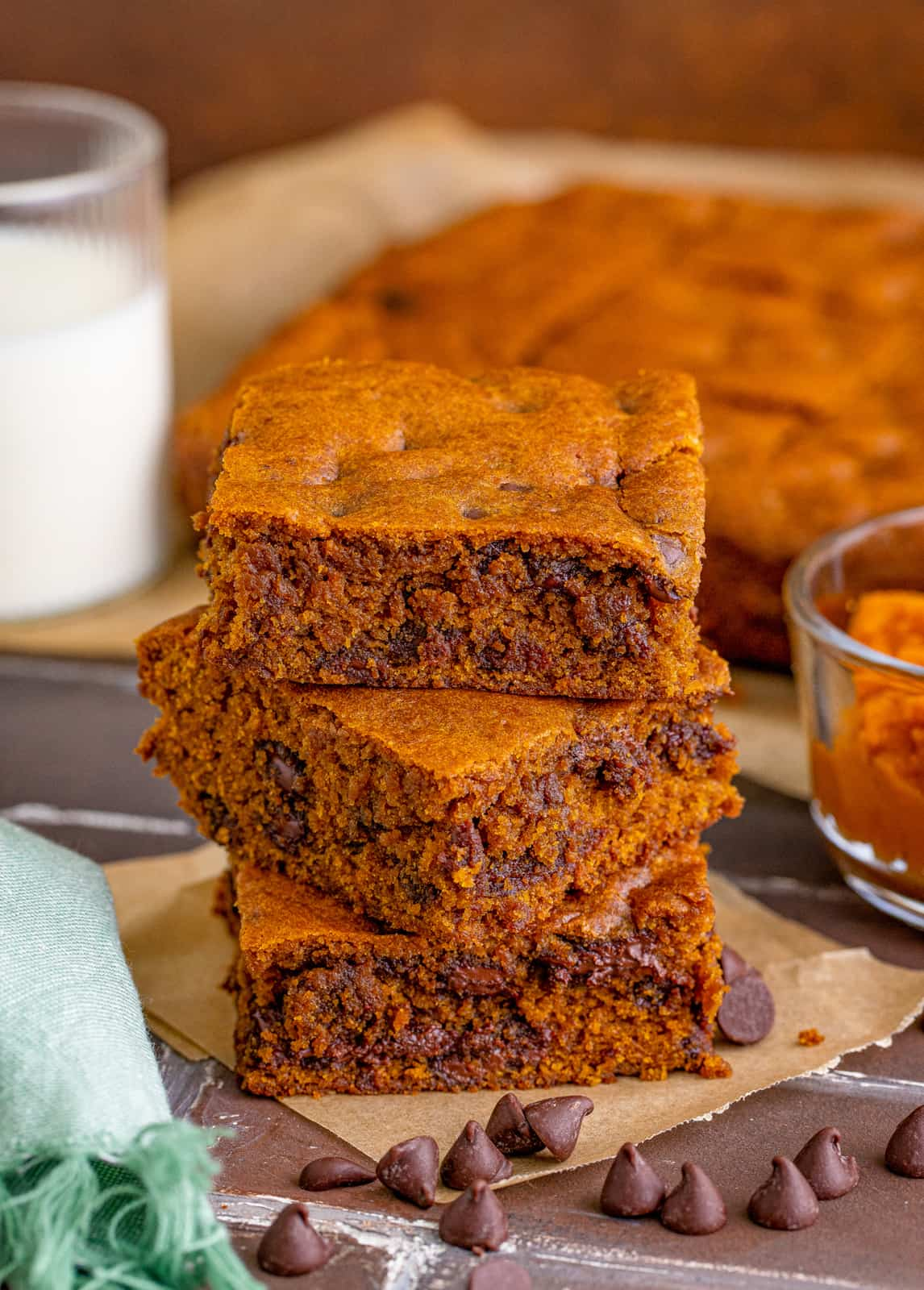 Three stacked Pumpkin Blondies on parchment paper with chocolate chips around it and glass of milk in background.