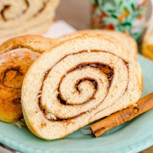 Slices of Cinnamon Swirl Bread on light blue/green plate with cinnamon stick square image.