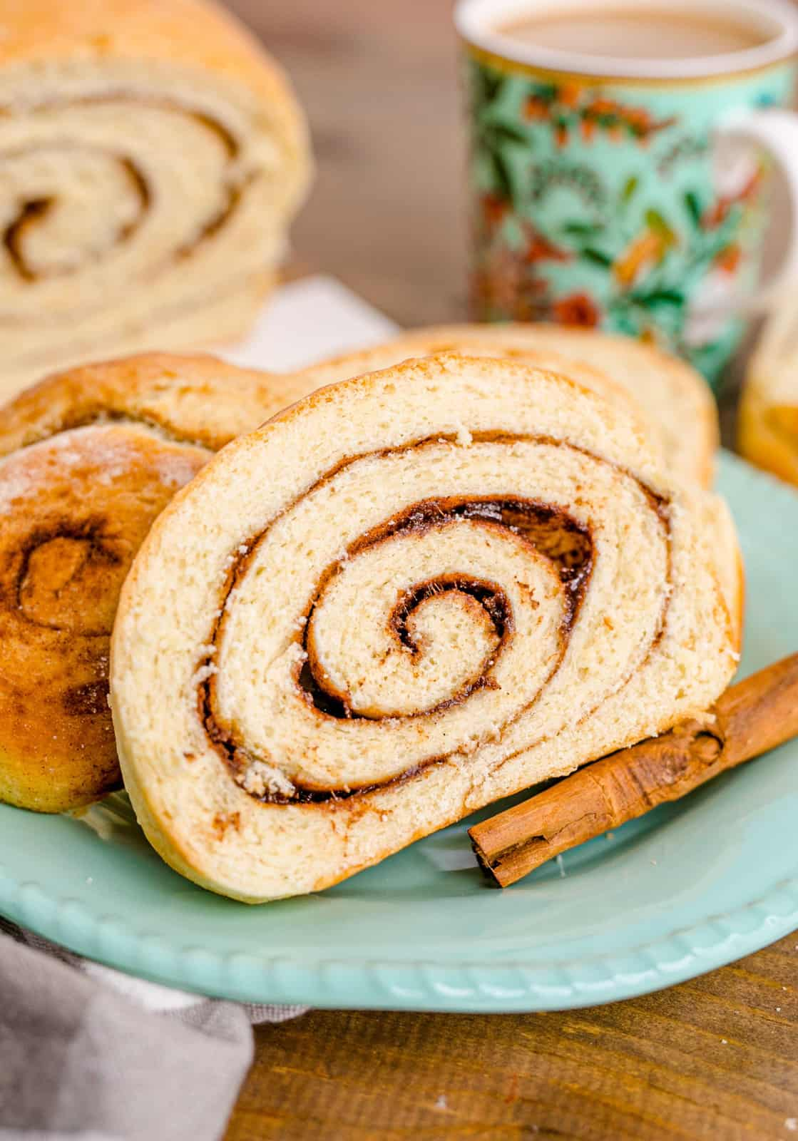 Slices of Cinnamon Swirl Bread on blue/green plate with cinnamon stick and cup of coffee in background.