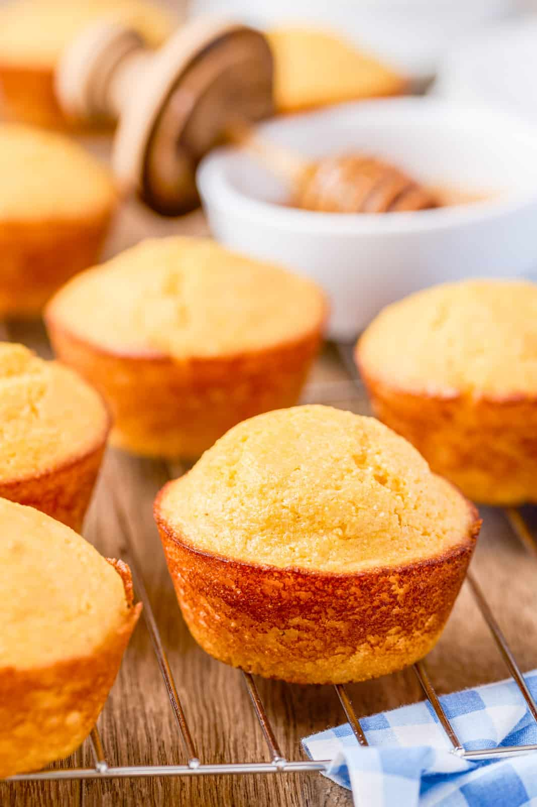 Finished Cornbread Muffins on wire rack with honey in background.