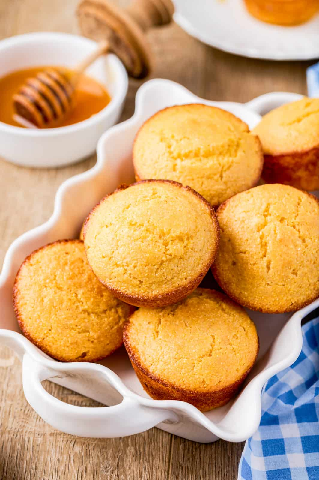 Stacked Cornbread Muffins in white dish with honey in background.