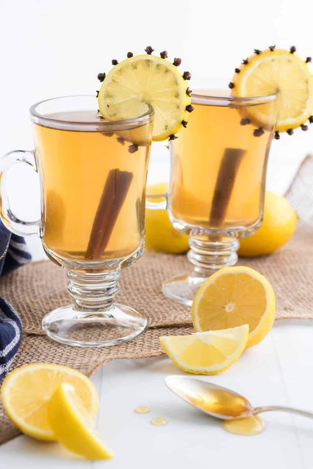 Hot Toddy Recipe in handled glasses with lemon slices and cinnamon sticks.