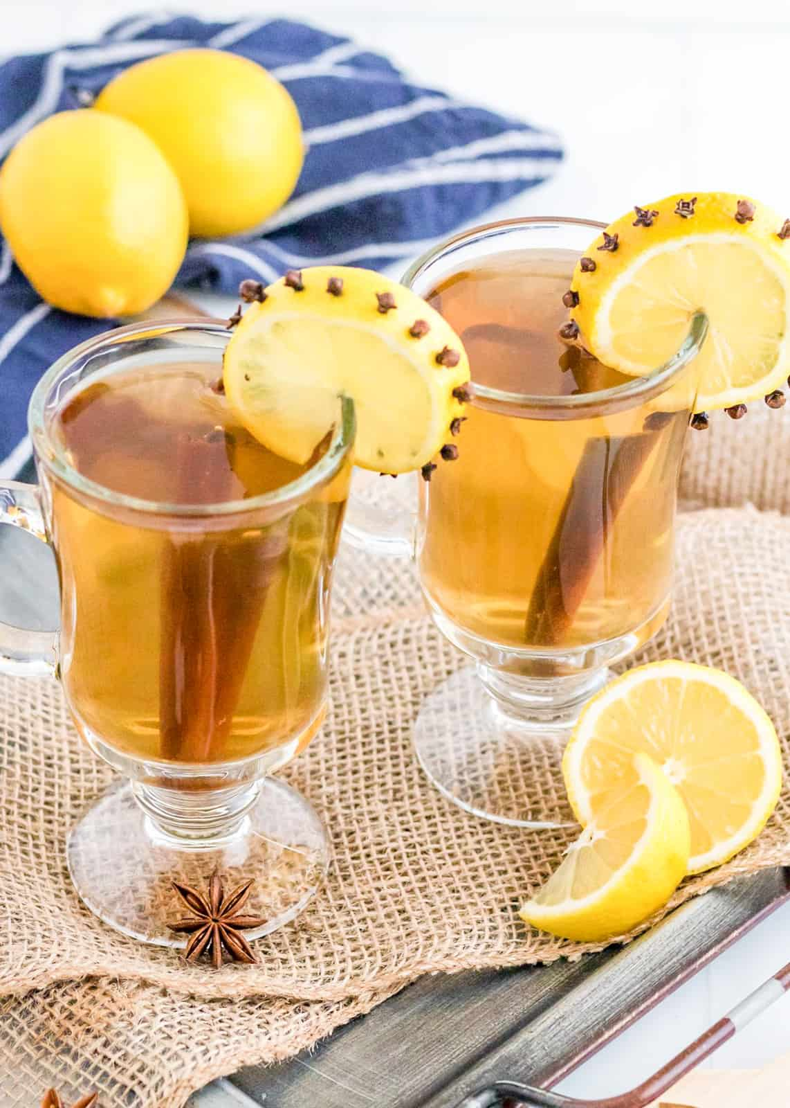 Two glasses overhead angle with Hot Toddy Recipe garnish with lemon and cinnamon sticks.