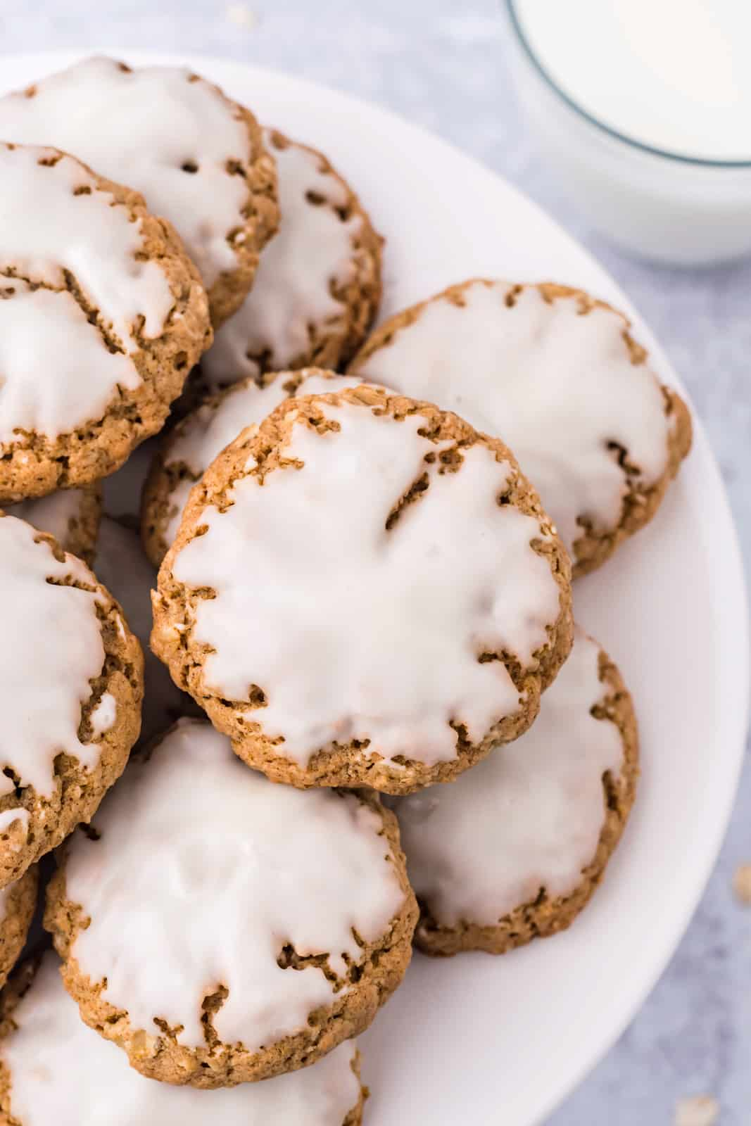 Stacked Iced Oatmeal Cookies overhead on white stand.