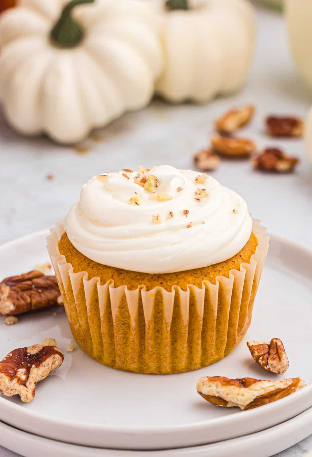 Close up of one Pumpkin Cupcake on white plate with chopped nuts.