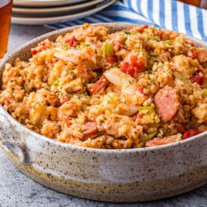 Square serving bowl of Jambalaya with plates in background.