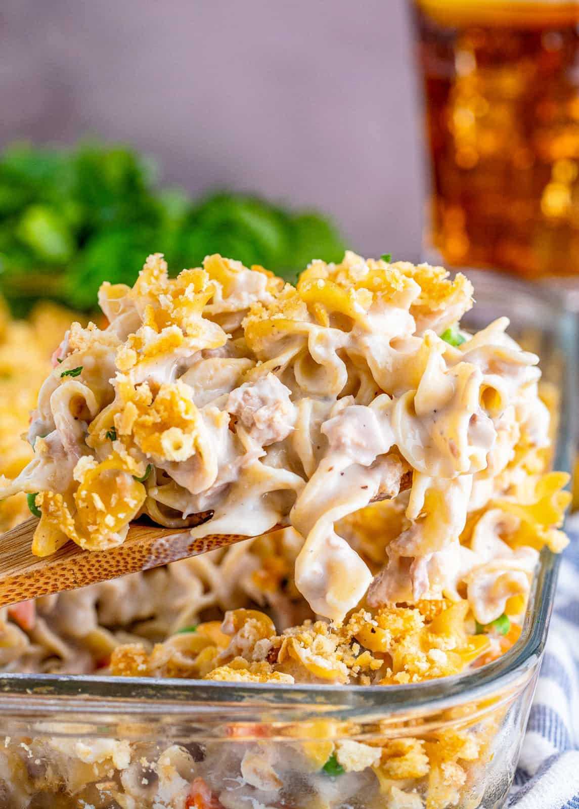 Wooden spoon scooping the Tuna Noodle Casserole Recipe out of baking pan.