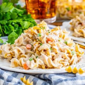 Square photo of Tuna Noodle Casserole on white plate with parsley and drink in background.