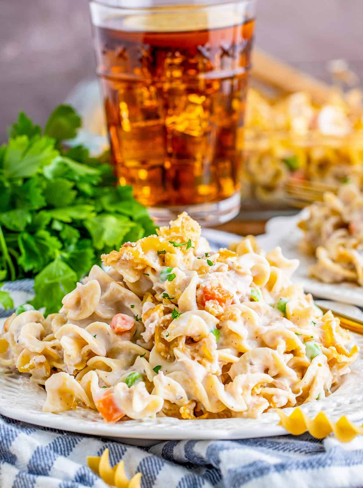 Tuna Noodle Casserole Recipe on white plate with parsley and drink in background.