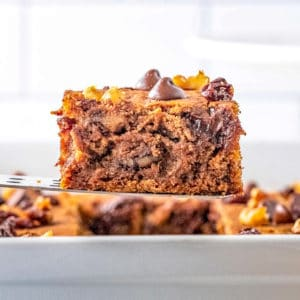 Square image of cake server holding up a slice of Applesauce Cake.