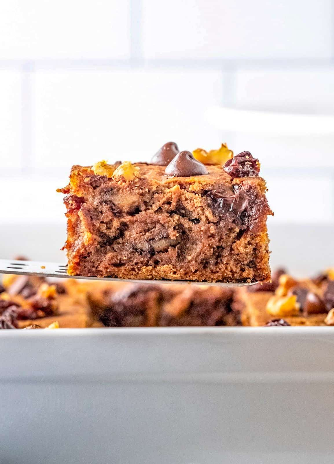Cake server holding up a slice of the Vintage Chocolate Chip Applesauce Cake out of pan.