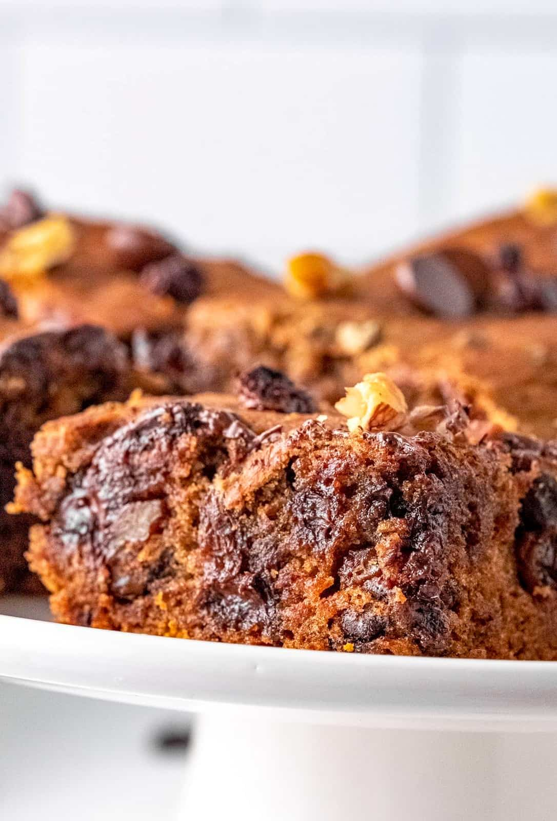 Close up of Vintage Chocolate Chip Applesauce Cake on white stand showing gooey chocolate chips.