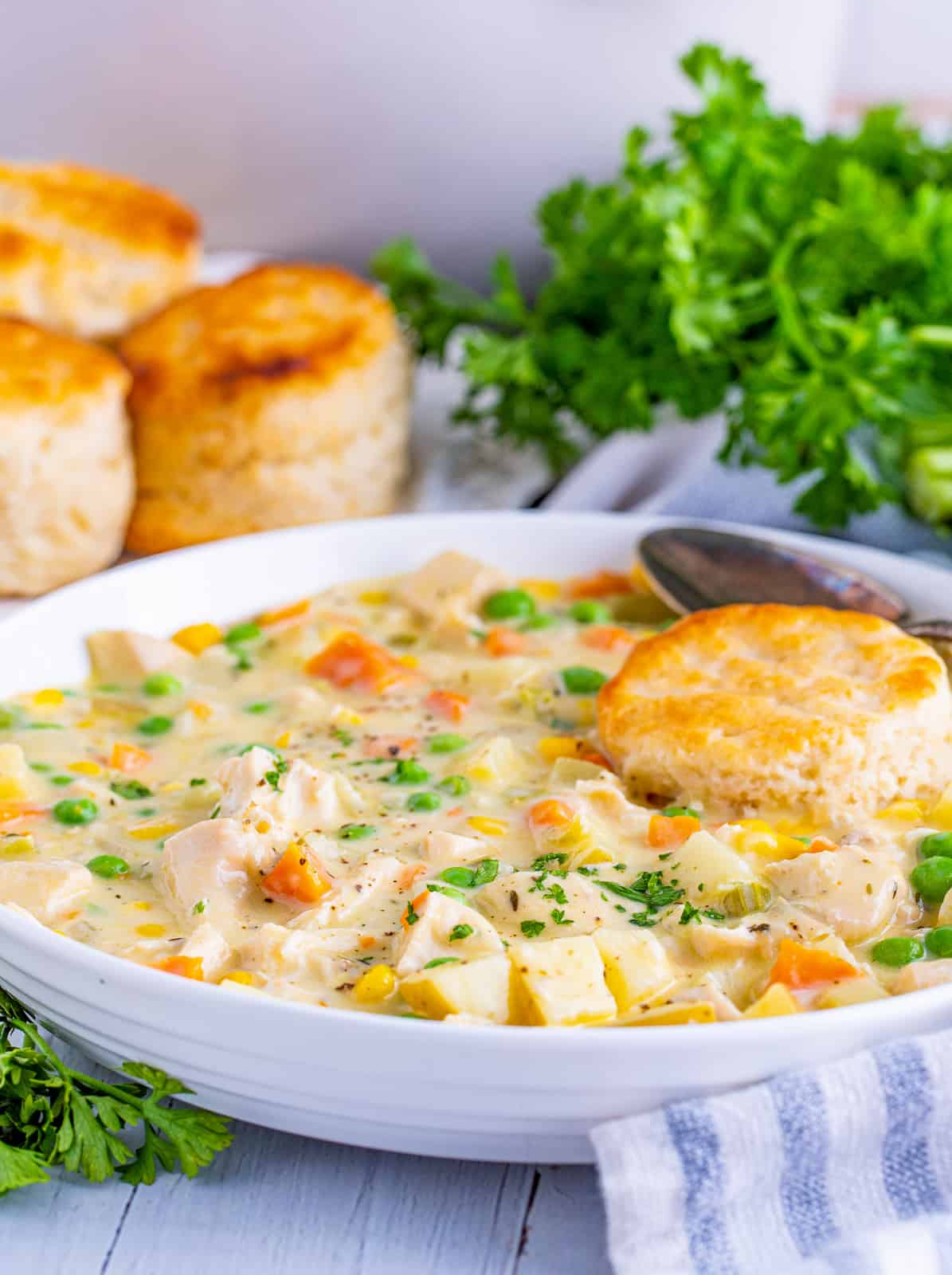 White bowl filled with Chicken Pot Pie Soup topped with a biscuit.