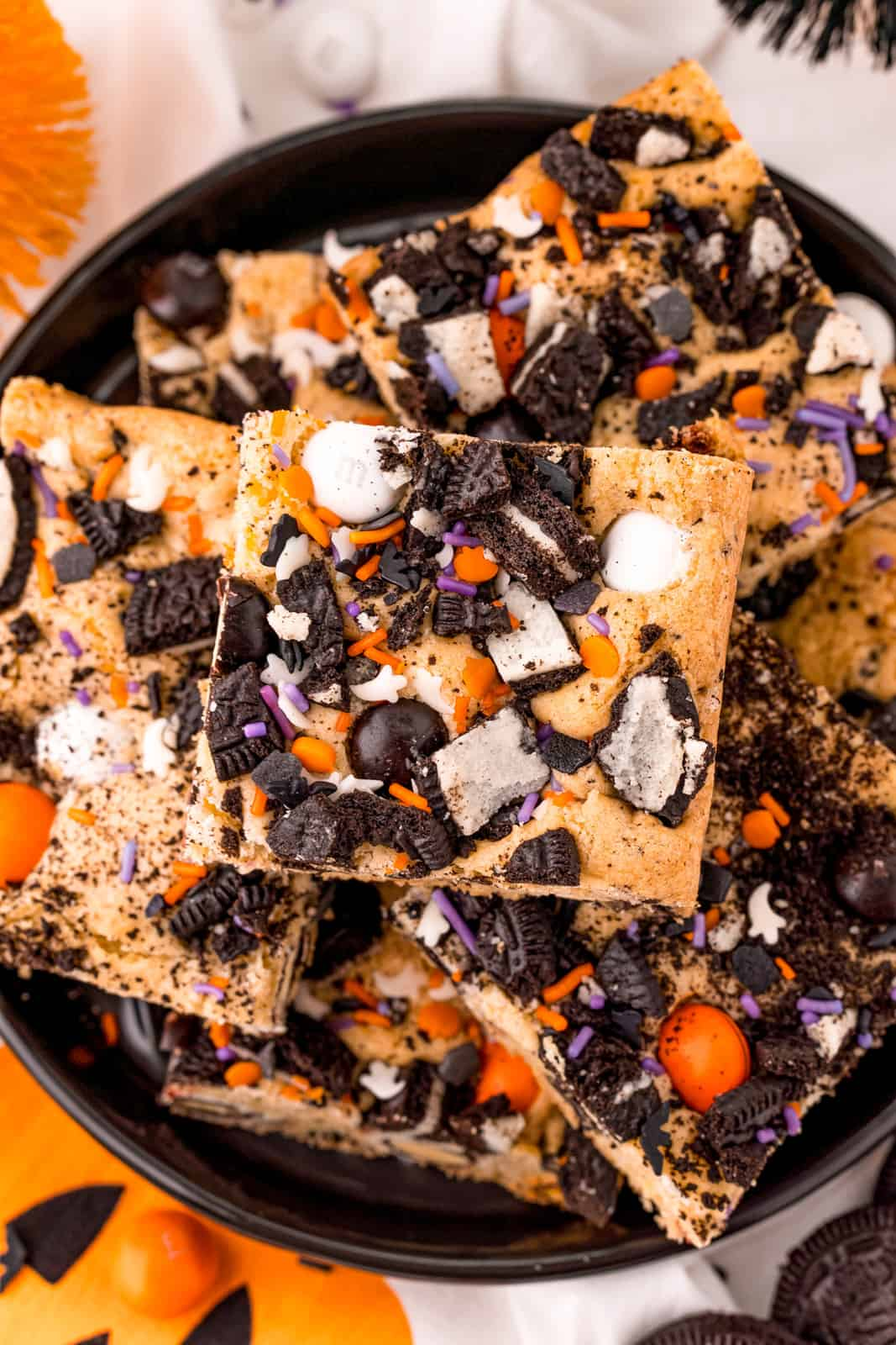 Stacked Halloween Cookie Bars on black plate.