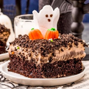 Square image of slice of Halloween Dirt Cake topped with pumpkins ahd ghost.