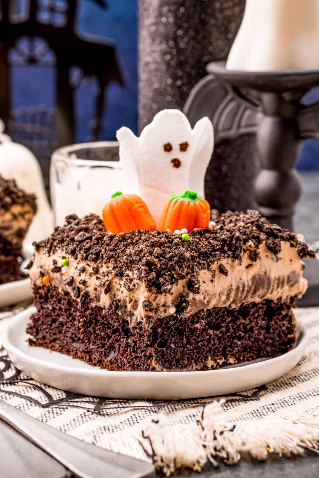 Slice of Dirt Cake on white plate with pumpkins and a ghost.