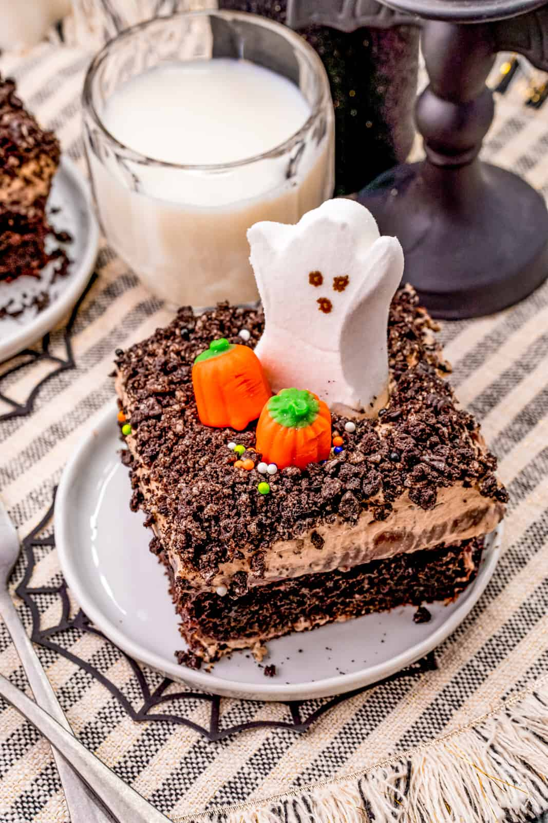 Overhead angled photo of a slice of cake on white plate decorated for Halloween with milk in back.