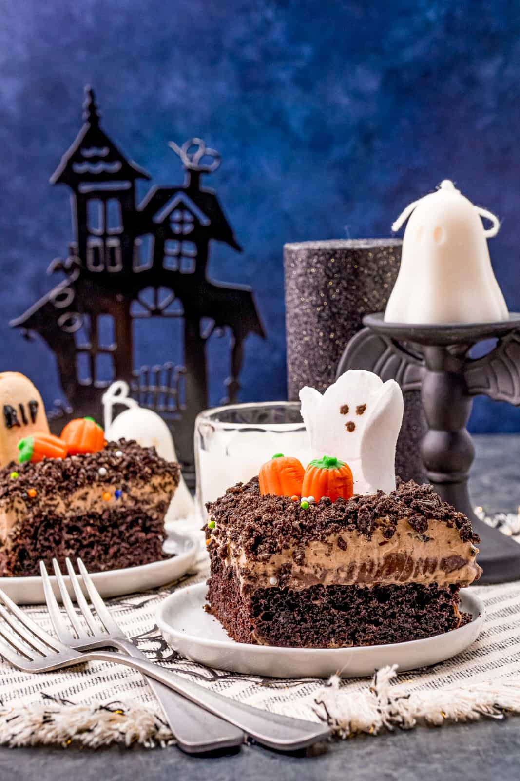 Two slices of Halloween Dirt Cake on plates with forks in front.