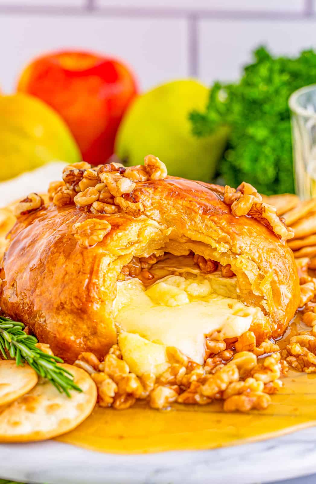 Honey Walnut Baked Brie Recipe with cheese oozing out of the center.