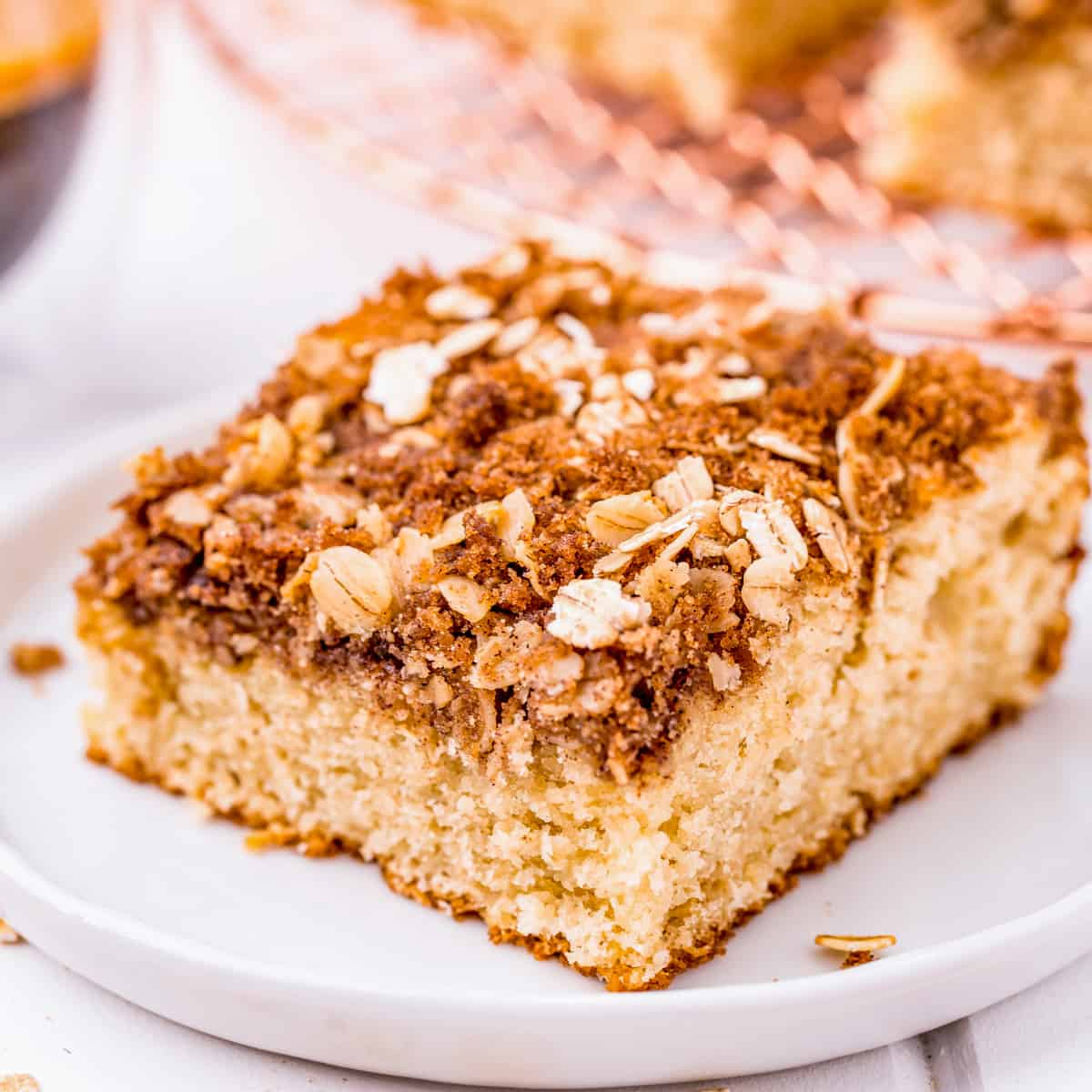 Square image of slice of Coffee Cake on white plate.