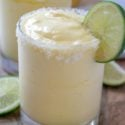 Frozen Pineapple Margaritas in clear glass surrounded by lime wedges and slices