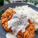 Pepper gravy drizzled over fried chicken piece on mashed potatoes